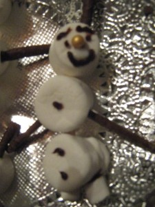 snowman made of white marshmallows with chocolate stick arms