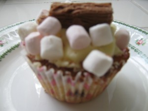 Vanilla cup cake with chocolate chips, buttercream icing, chocolate flake and mini marshmallows